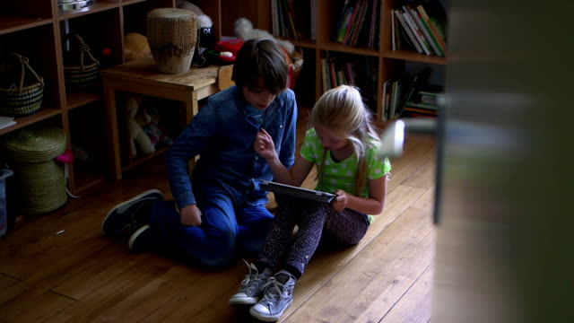 Children playing with digital tablet in bedroom