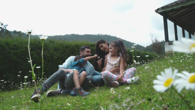 stockvideo's en b-roll-footage met kinderen spelen met bloemen naast hun ouders - latijns amerikaanse en hispanic etniciteiten