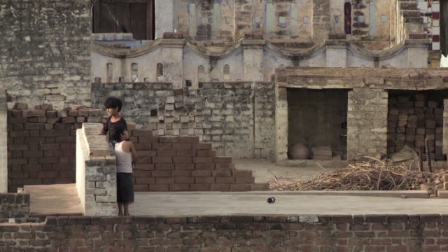 MS HA Children playing with kite on rooftop in foreground / Agra, Uttar Pradesh, India
