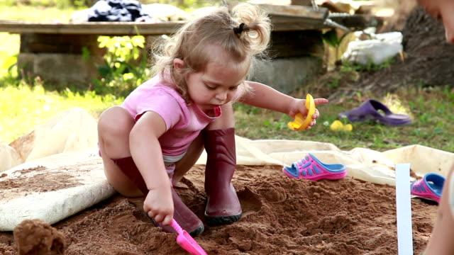 vídeos y material grabado en eventos de stock de niños jugando con arena en el patio trasero - work tool
