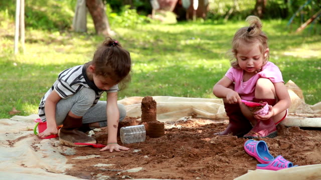 kinder spielen mit sand im hinterhof - schmutzig stock-videos und b-roll-filmmaterial