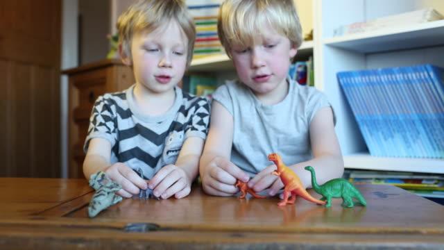 vídeos de stock, filmes e b-roll de children playing with toy dinosaurs - animal de brinquedo