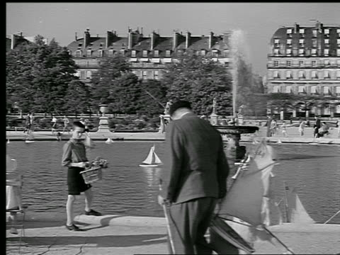 B/W 1936 children playing with toy sailboats in fountain in Place du Carrousel / Paris, France