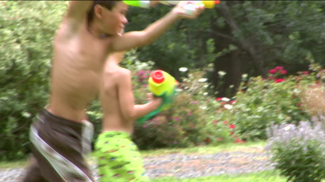 ws zi ms pan children playing with water guns on lawn / sherman, ct, usa - squirt gun stock videos and b-roll footage
