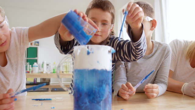 children pouring colour into a jar with water in a science experiment - pouring stock videos & royalty-free footage