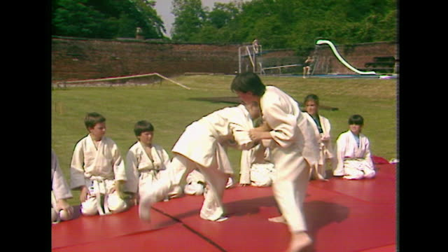 children practice judo throws on an outdoor crash mat; 1984 - martial arts stock videos & royalty-free footage