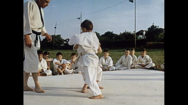 montage children practicing judo, britain - asiatischer kampfsport stock-videos und b-roll-filmmaterial