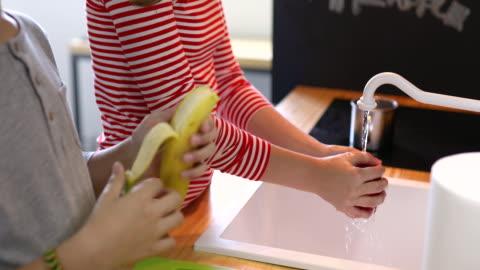 vídeos de stock, filmes e b-roll de crianças, preparar a salada de frutas - lavar