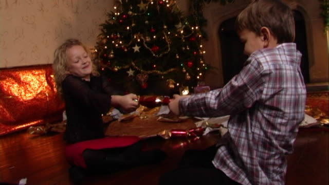 children pulling christmas cracker. - christmas cracker stock videos and b-roll footage