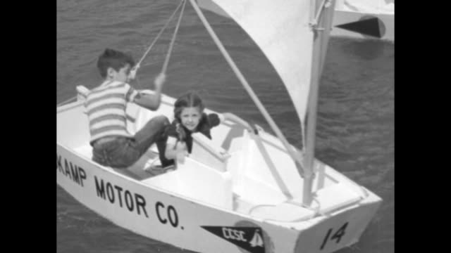 children push prams off the beach / vs the prams cluster then sail around a floating dock / one boy inserts the keel as another mans the rudder / boy... - kiel rumpf stock-videos und b-roll-filmmaterial