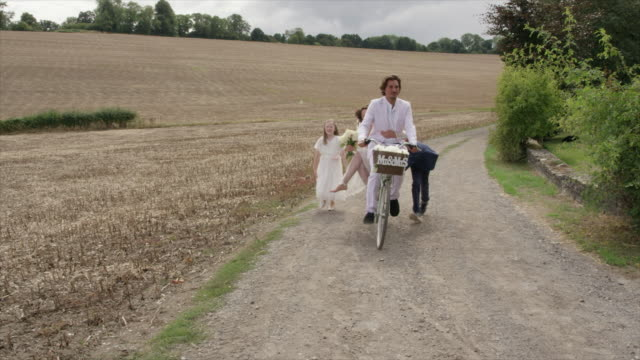 children pushing bicycle with newlyweds - sposa video stock e b–roll