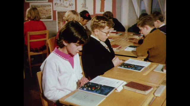 MONTAGE Children reading and discussing illustrated book in the classroom in England / United Kingdom