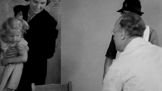 1940 montage children receiving health care services at british area clinic / united kingdom - impfung stock-videos und b-roll-filmmaterial