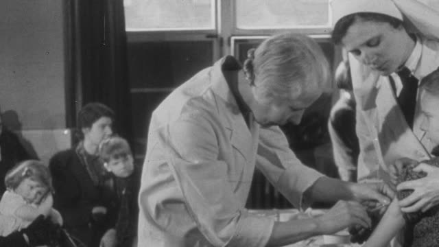 1941 pan children receiving the vaccination for diphtheria in a clinic / united kingdom - diphtherie stock-videos und b-roll-filmmaterial