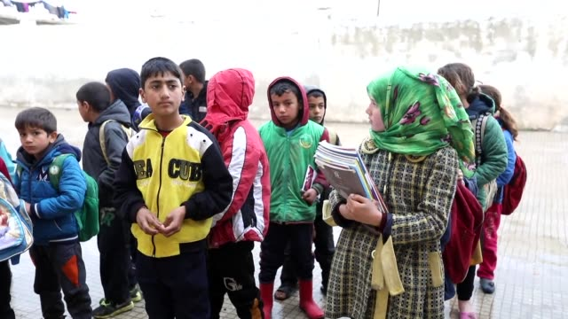 Children recited their lessons in class and played amid the rubble of their destroyed schools Sunday in villages of Hama and Idlib provinces in war...