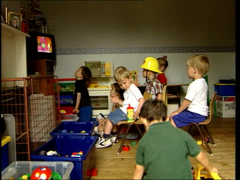 research shows to much tv can be harmful; england: int group of young children sitting in playroom watching tv cms small boy wearing fireman's hat as... - sideways glance stock videos & royalty-free footage