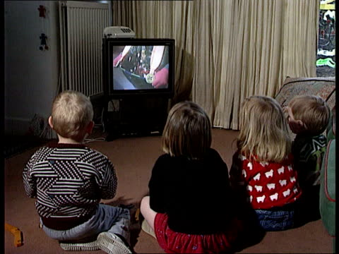 research shows to much tv can be harmful int bv four small children sitting on floor watching tv group of young children playing with toys in yard - fernsehserie stock-videos und b-roll-filmmaterial