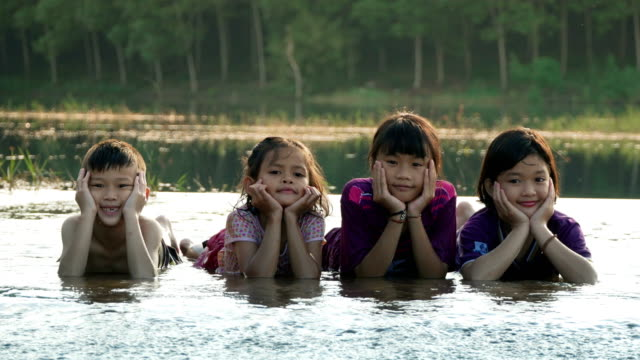 children rest on chin in water - reclining stock videos and b-roll footage