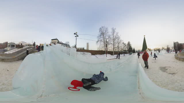 vídeos de stock e filmes b-roll de children ride down an ice slide near the new year's eve.  360-degree view of the central square of the city of krasnoyarsk on the eve of christmas. - panorama equiretangular