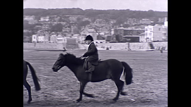 children ride horses in front of the winter garden pavilion on the beach at weston-super-mare - 1940 1949 stock-videos und b-roll-filmmaterial