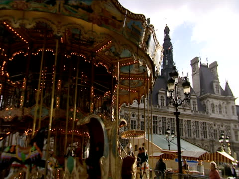 Children ride horses on old-fashioned carousel in town square Paris