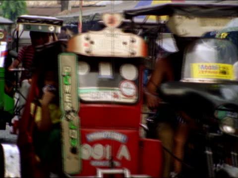children ride in pedicabs or walk on the sidewalks as they go to school. - rikscha stock-videos und b-roll-filmmaterial