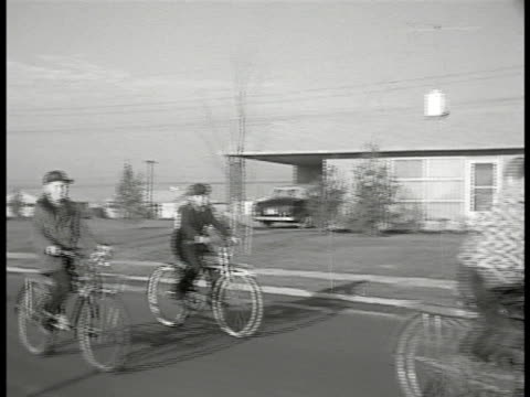 LEVITTOWN PENNSYLVANIA Children riding bicycles on neighborhood road girl bigger brother waving from sidewalk couple leaving Sales counter workman...