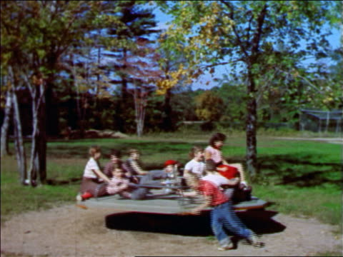 1957 children riding spinning merry-go-round on playground / new jersey / industrial - 1957 stock videos & royalty-free footage