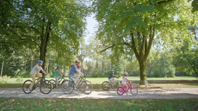TS Children riding their bikes through the park with their parents and grandparents