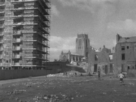 stockvideo's en b-roll-footage met children run across derelict land with liverpool cathedral in the distance 1964 - liverpool engeland