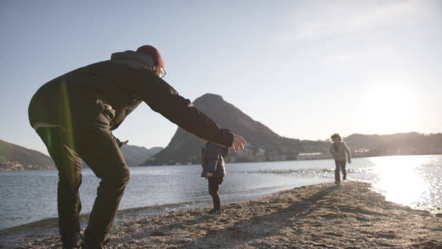 children run into fathers arms at sunset by the lake - famiglia con due figli video stock e b–roll