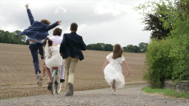 children running after bicycle - イングランド南西部点の映像素材/bロール