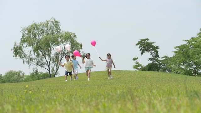 children running and holding a balloon on the lawn - 芝生点の映像素材/bロール