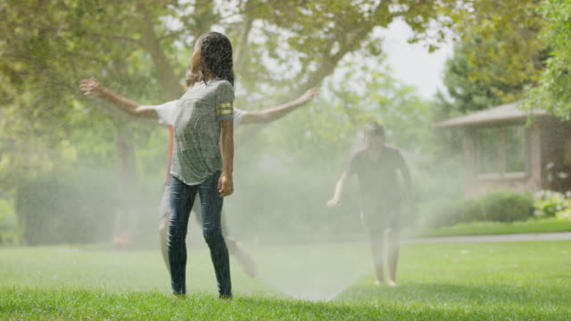 children running and jumping through sprinkler / provo, utah, united states - provo stock-videos und b-roll-filmmaterial