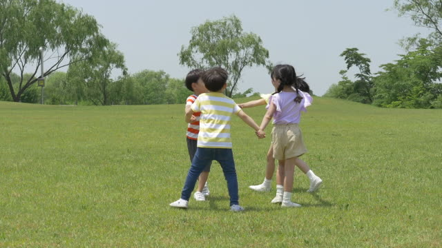 children running and playing on the lawn - 芝生点の映像素材/bロール