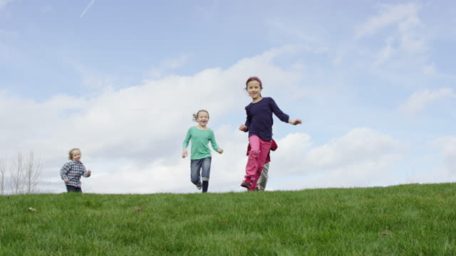 children running and playing tag outdoors - human age stock videos & royalty-free footage
