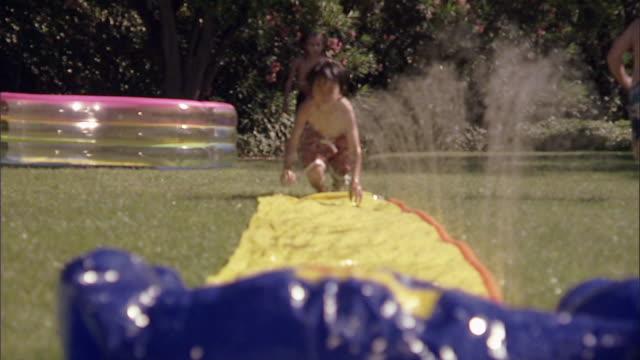 slo mo ws children running and sliding on backyard water slide / los angeles, california, usa - acquascivolo video stock e b–roll