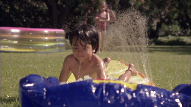 vidéos et rushes de slo mo ws children running and sliding on backyard water slide / los angeles, california, usa - pataugeoire