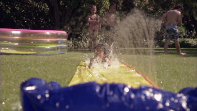 slo mo ws children running and sliding on backyard water slide / los angeles, california, usa - water slide stock videos & royalty-free footage