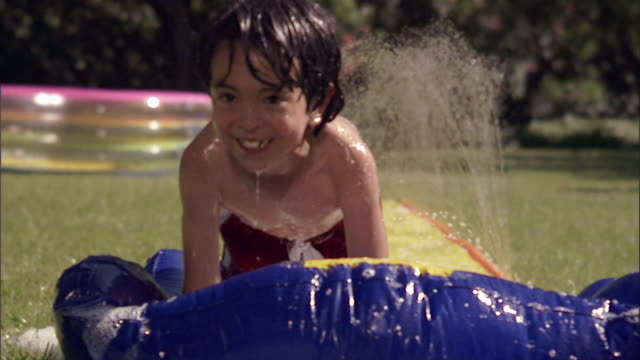 slo mo ws children running and sliding on backyard water slide / los angeles, california, usa - low angle view stock videos & royalty-free footage