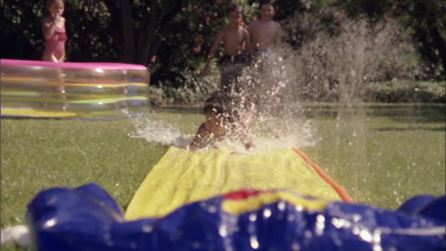 slo mo ws children running and sliding on backyard water slide / los angeles, california, usa - rutschen stock-videos und b-roll-filmmaterial