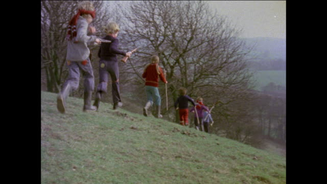 MONTAGE Children running down a hill pretending to be Apaches / United Kingdom