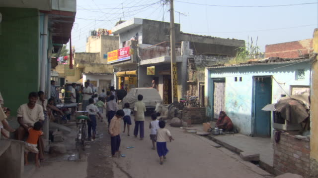 ws children running down street past shops in poor neighborhood, districts of delhi, india - delhi stock videos & royalty-free footage