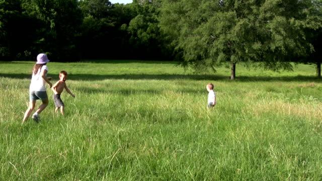 vídeos de stock, filmes e b-roll de crianças correndo em um campo - brincadeira de pegar