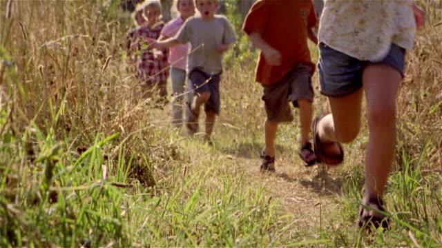 TU children running in a row thru field with barn in background / Fall City, Washington