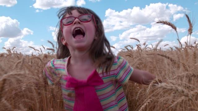 vídeos de stock, filmes e b-roll de crianças que funcionam no trigo - de braço levantado