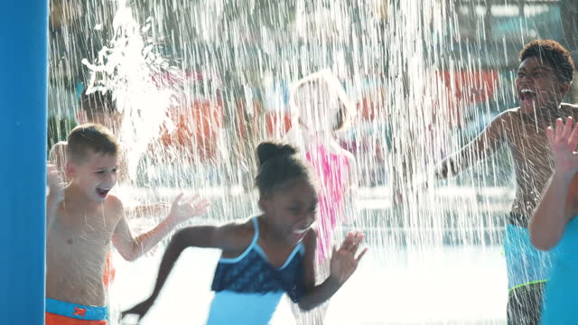 children running through falling water at waterpark - 8 9 years stock videos & royalty-free footage