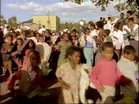vidéos et rushes de ms children running through street, palm sunday, ethiopia, africa - village