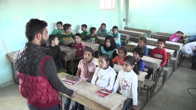 Children rushed out into the schoolyard for break time on the first day of classes in the Syrian town of Manbij ignoring the Islamic State group...