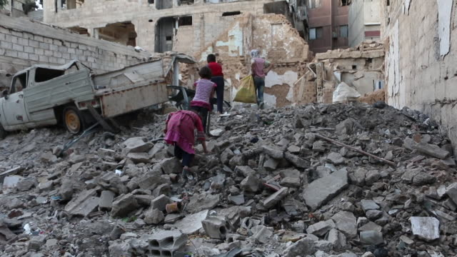children searching for firewood amongst rubble after air strikes in eastern ghouta syria - syrien stock-videos und b-roll-filmmaterial